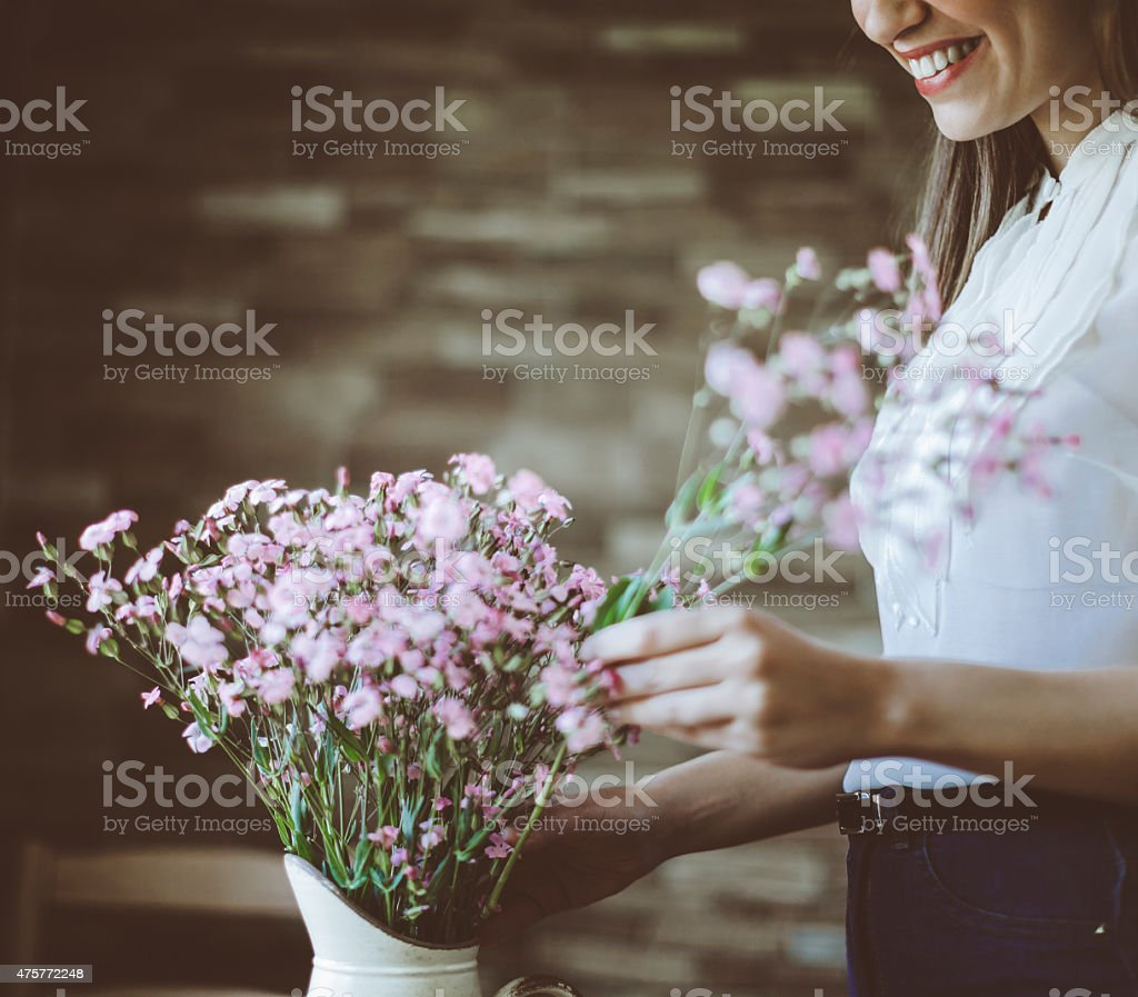Young Latin woman arranging flowers stock photo