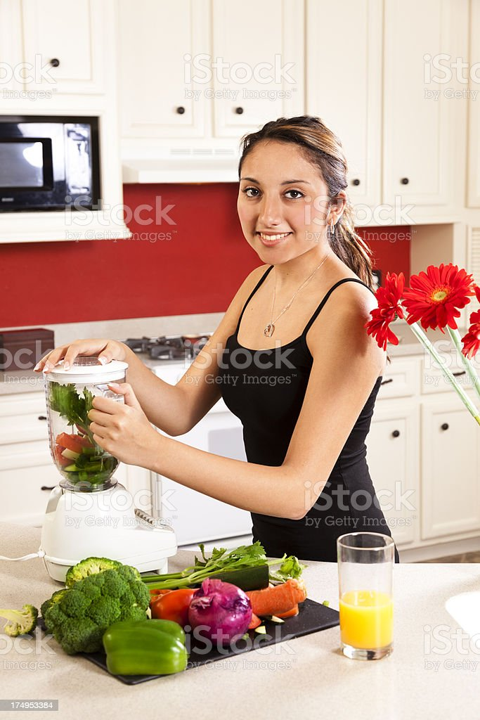 Young Latin woman blending vegetables for healthy meal in kitchen royalty-free stock photo