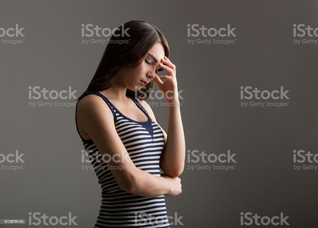 Young latin woman holding forehead stock photo