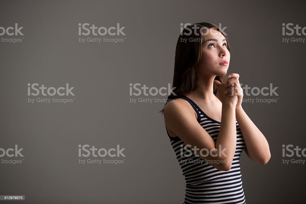 Young latin woman holding hands together stock photo