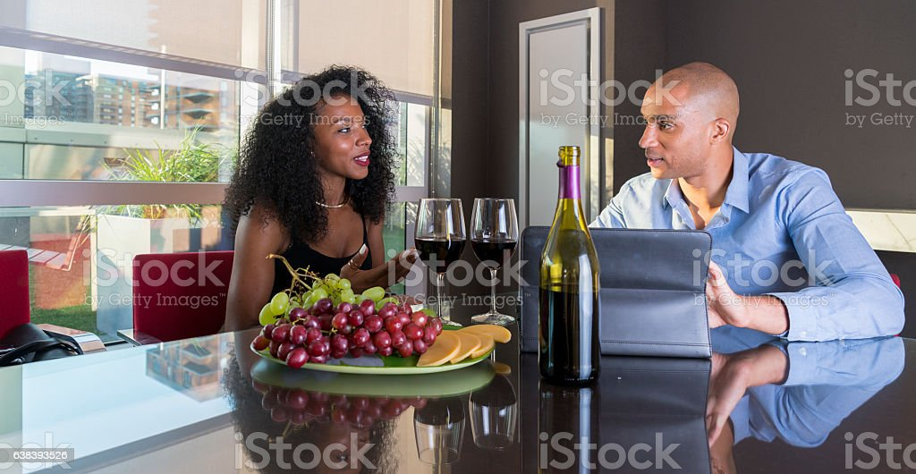 Young Latino couple have dinner in high floor apartment stock photo