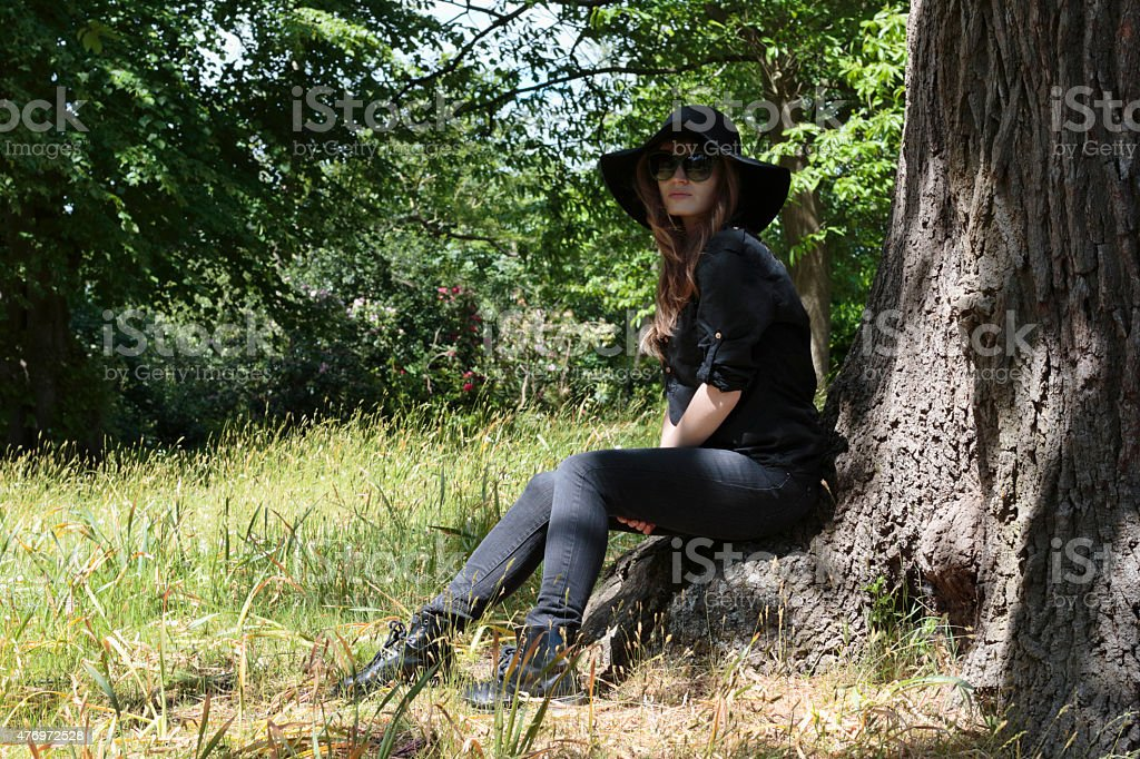 Young Latvian tree girl outdoors sitting on tree root stock photo