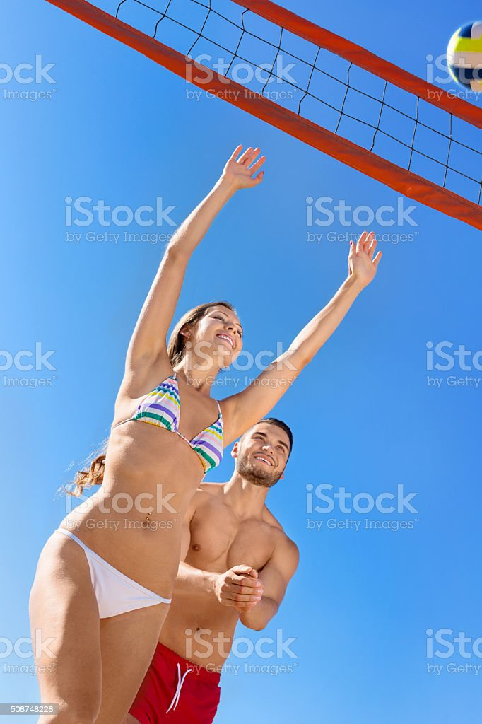 Young laughing couple playing volleyball stock photo