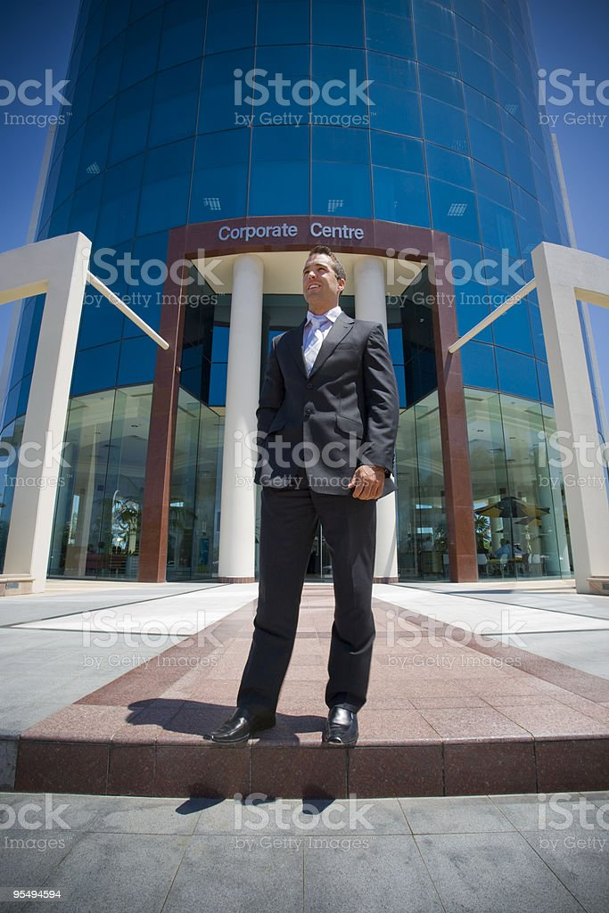 young lawyer in suit smiling standing outside corporate highrise royalty-free stock photo