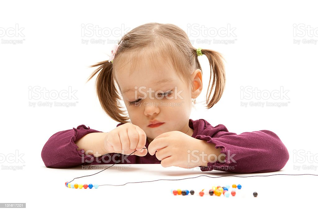 Young little girl beading on white background stock photo
