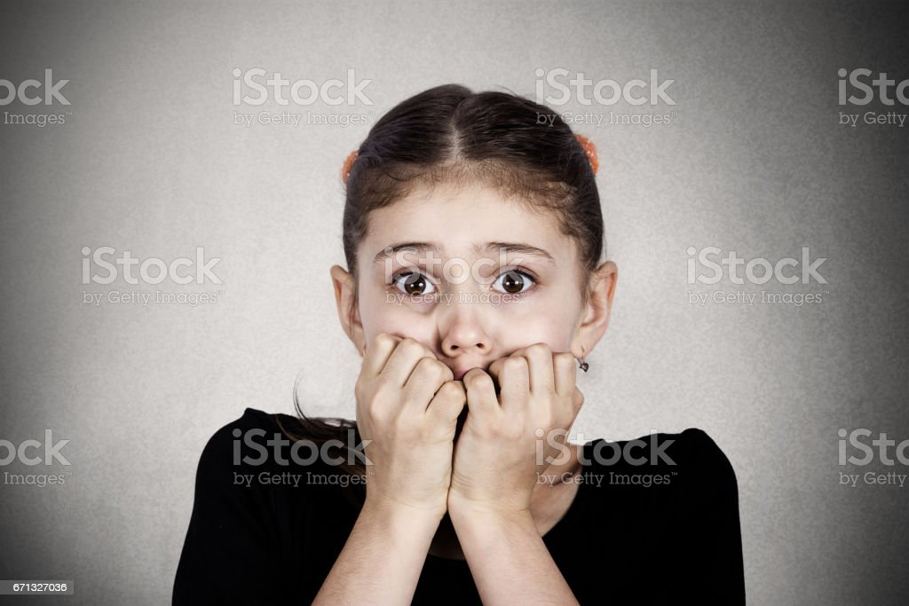 young little girl biting her finger nails, looking at you with fear of something stock photo