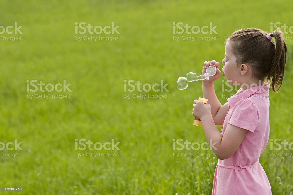 A young little girl blowing bubbles in nature royalty-free stock photo