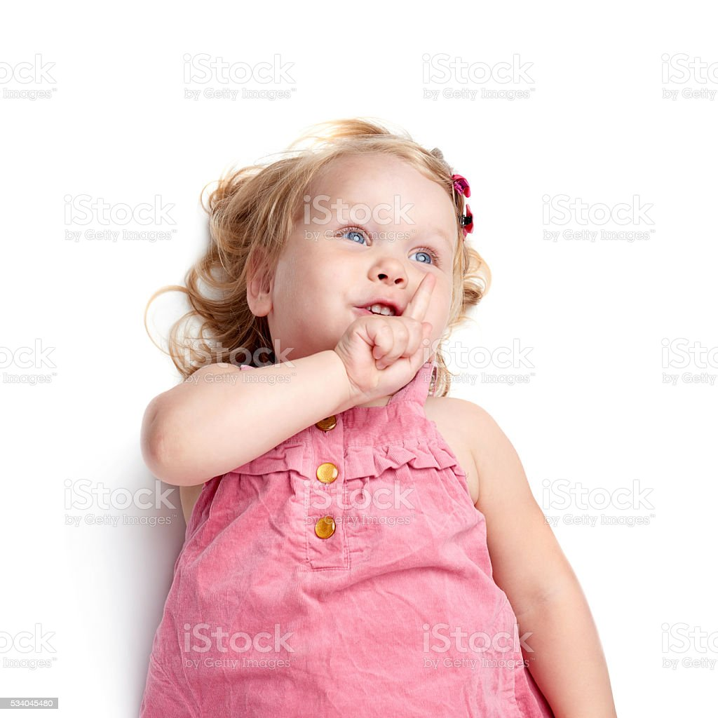 Young little girl lying over isolated white background stock photo