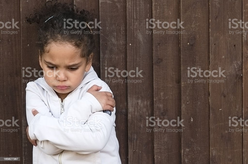 Young little girl with arms crossed and sad stock photo