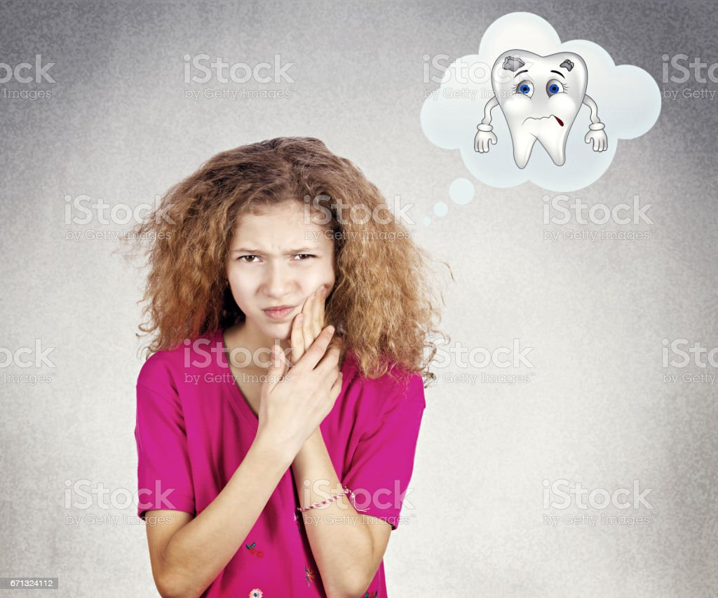 young little girl with sensitive tooth ache, crown problem touching outside mouth with hand, stock photo