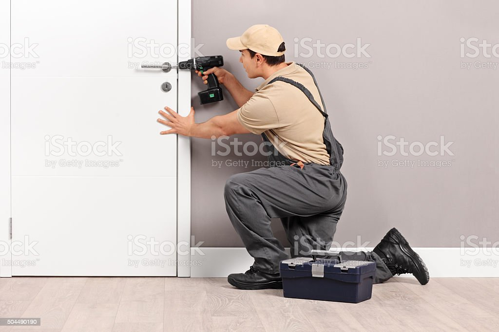 Young locksmith installing a lock on a door stock photo