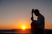 Young lonely guitarist playing on acoustic guitar