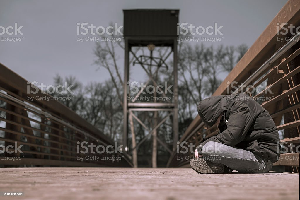 young lonely homeless man sitting on bridge alone stock photo