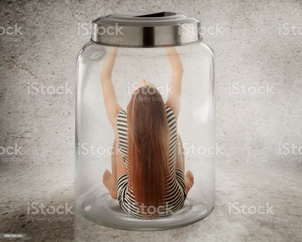 Young lonely woman sitting in glass jar stock photo