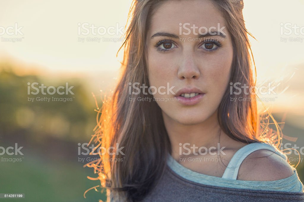 Young long brown hair woman portrait on sunset in nature stock photo