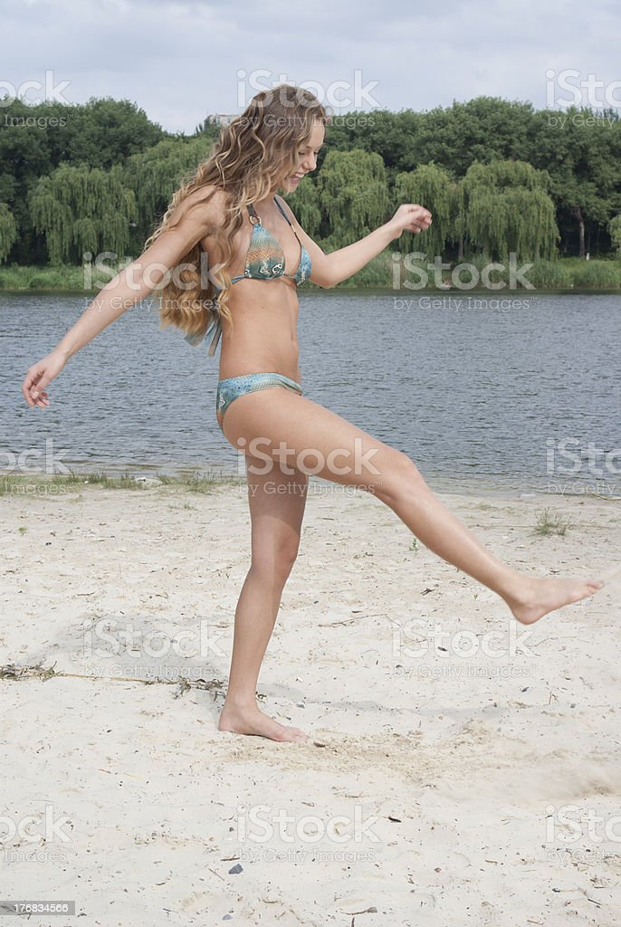 Young long-haired attractive woman in bikini on river beach royalty-free stock photo