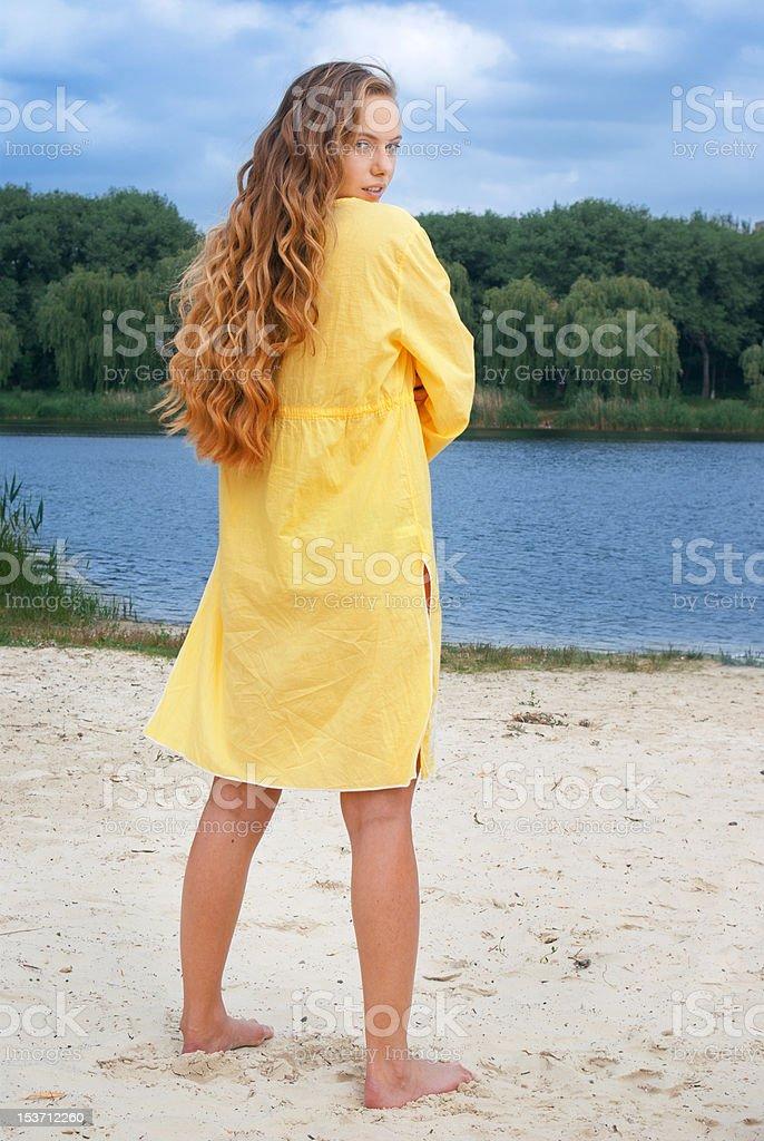 Joven de pelo largo atractiva mujer en amarillo sobre río Atuendo de playa foto de stock libre de derechos