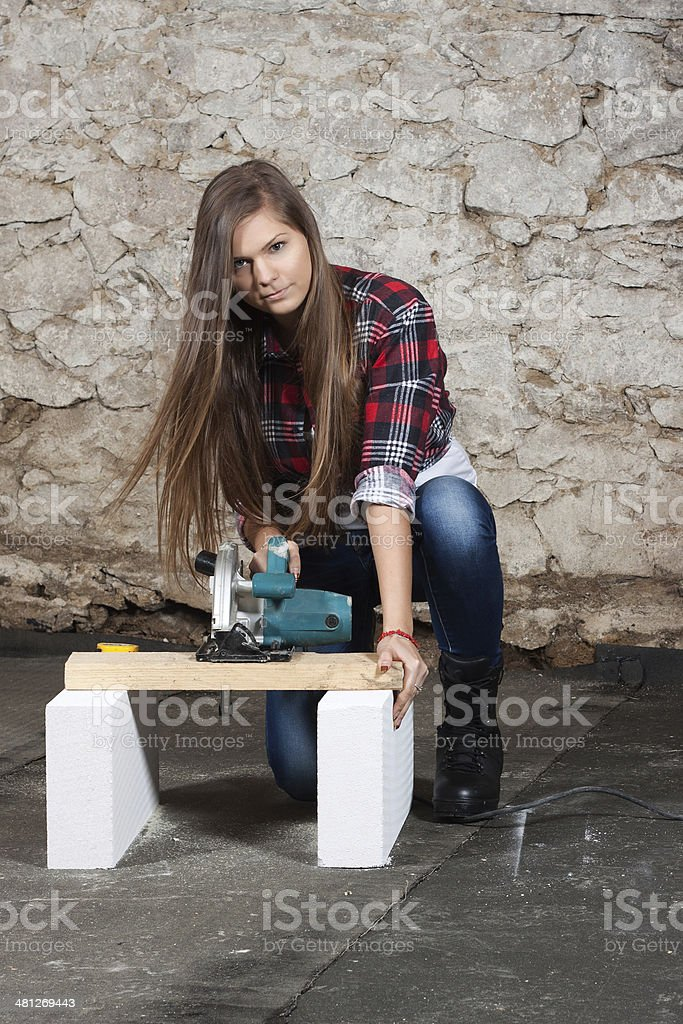 Young long-haired woman with a circular saw stock photo