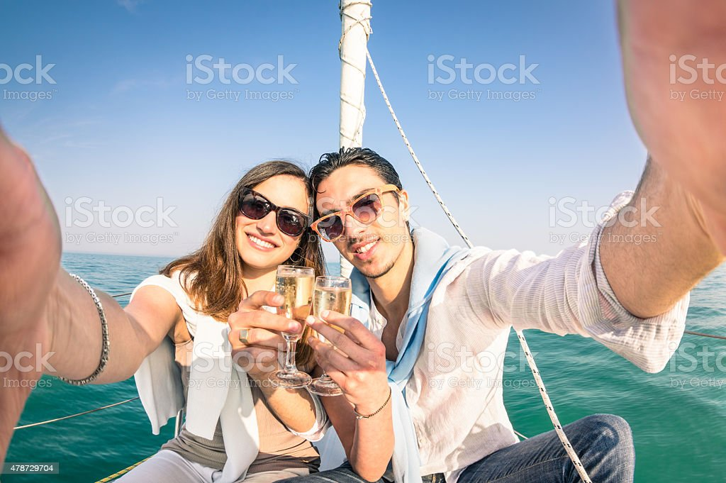 Young love couple taking selfie on sailing boat with champagne stock photo