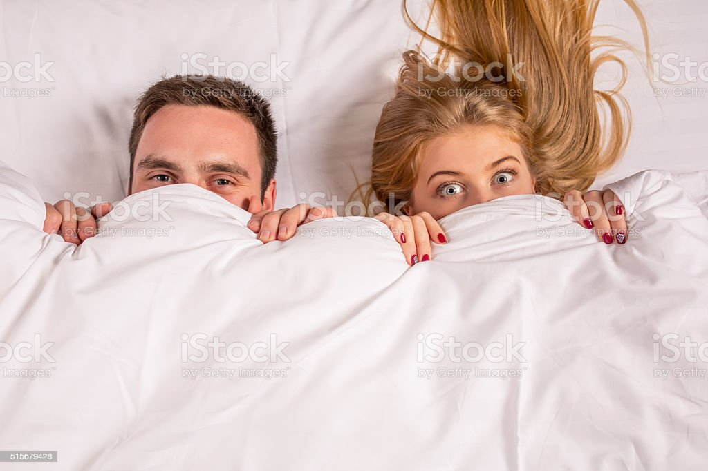 Young lovely couple lying in a bed, looking at camera stock photo