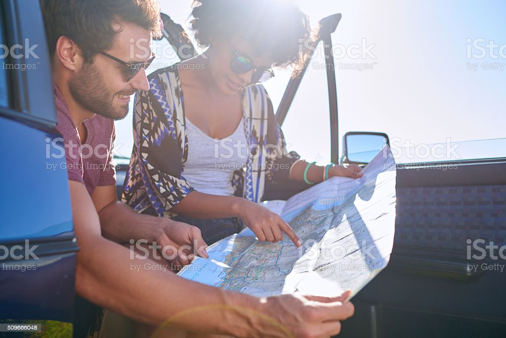 Young lovely couple using  map during roadtrip stock photo