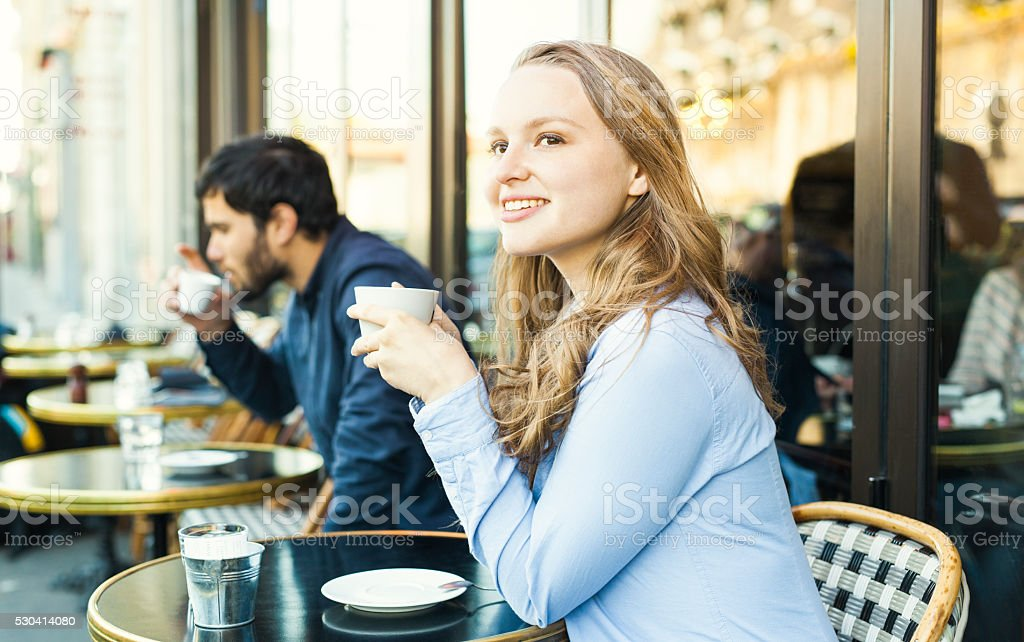 Young Lovely Woman Having Coffee Break in a Sidewalk Cafeteria stock photo