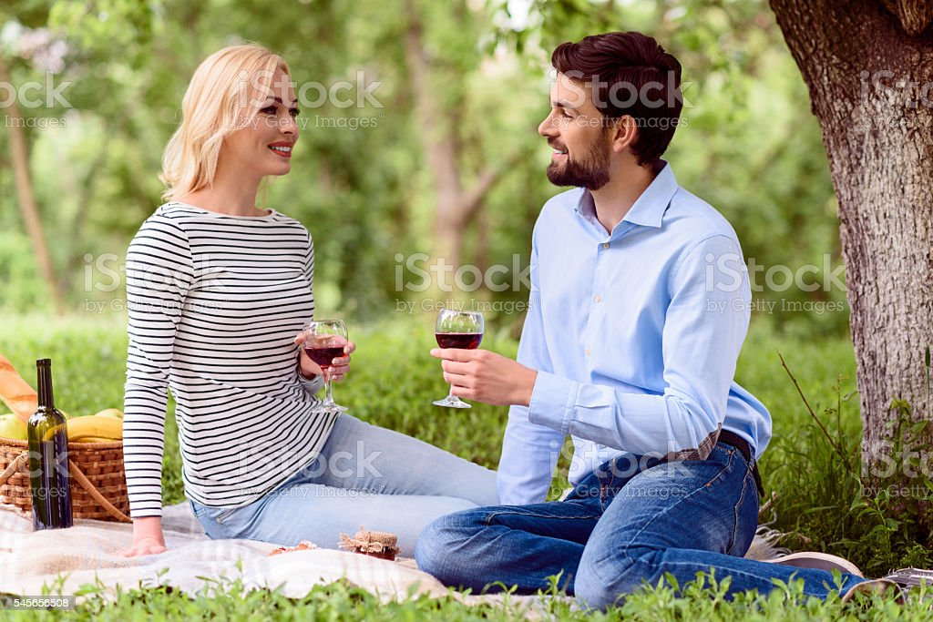 Young lovers drinking wine in nature stock photo
