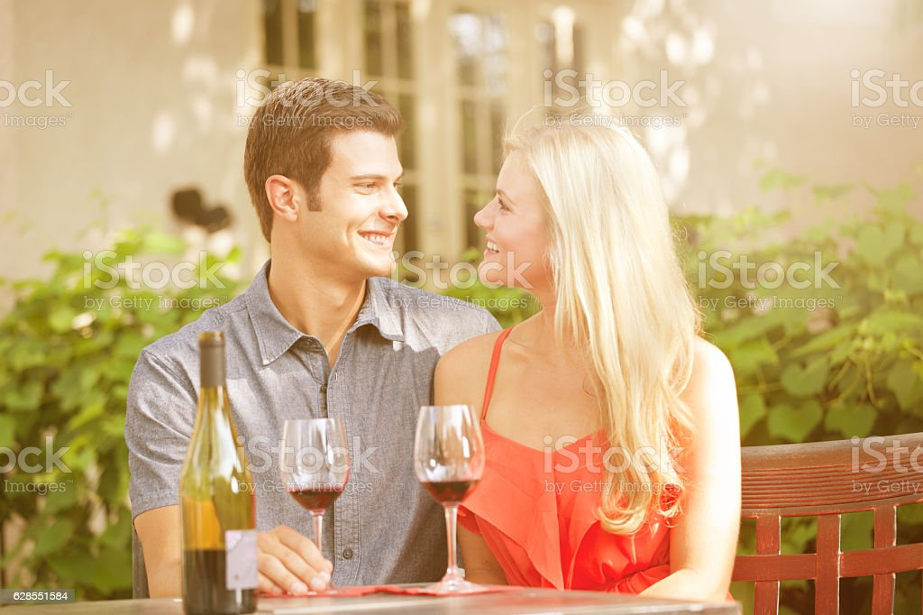 Young Lovers Enjoying Glass of Wine in Outdoor Restaurant stock photo