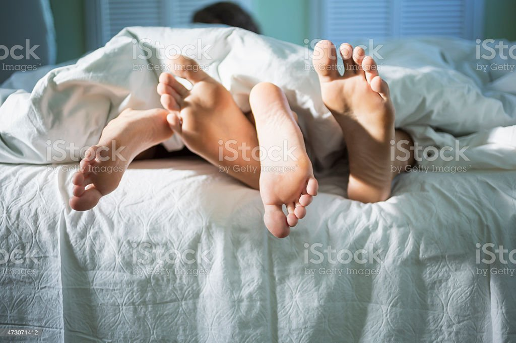 Young lovers under the covers in the morning stock photo