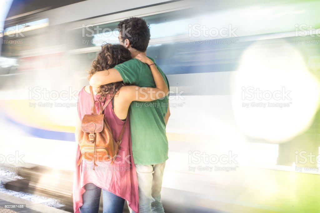 A young loving couple embracing while a train is moving on the background stock photo