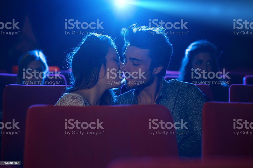 Young loving couple kissing at the cinema stock photo