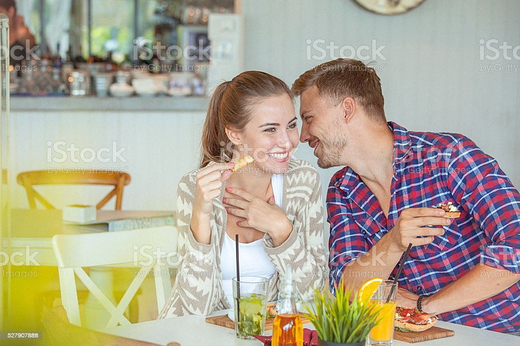 Young loving couple pleasantly chatting on a date in restaurant stock photo