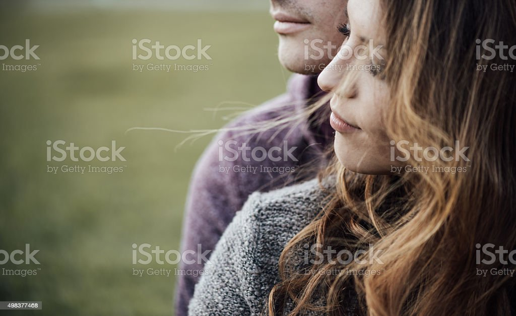 Young loving couple outdoors sitting on grass, hugging and looking...