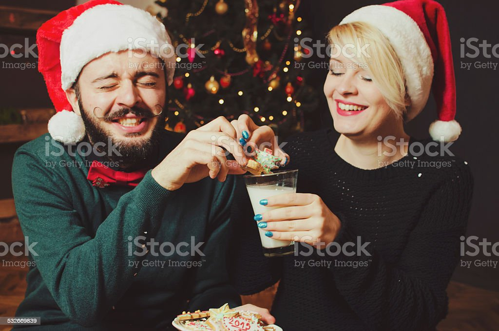 Young loving couple wearing Santa hats, eating cookies at home stock photo