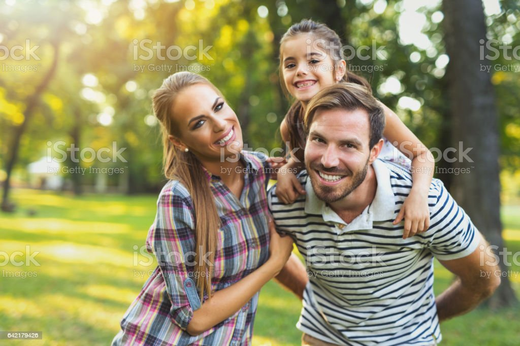 Young loving family having fun in the park. stock photo