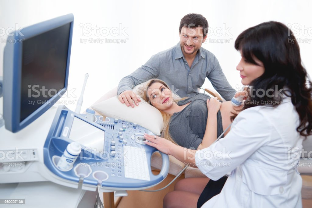 Young loving pregnant couple visiting doctor together stock photo
