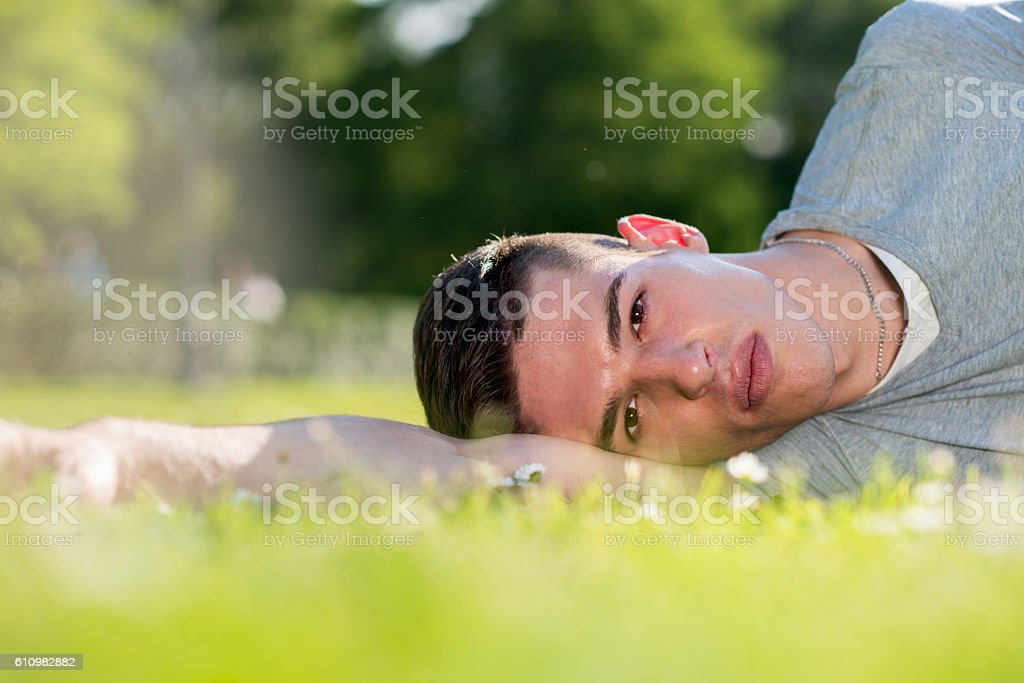 Young lying on grass during springtime. stock photo
