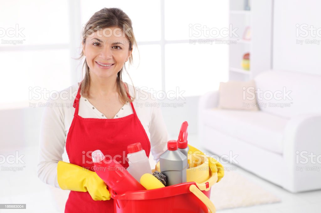 Young maid with bucketful looking at camera. stock photo