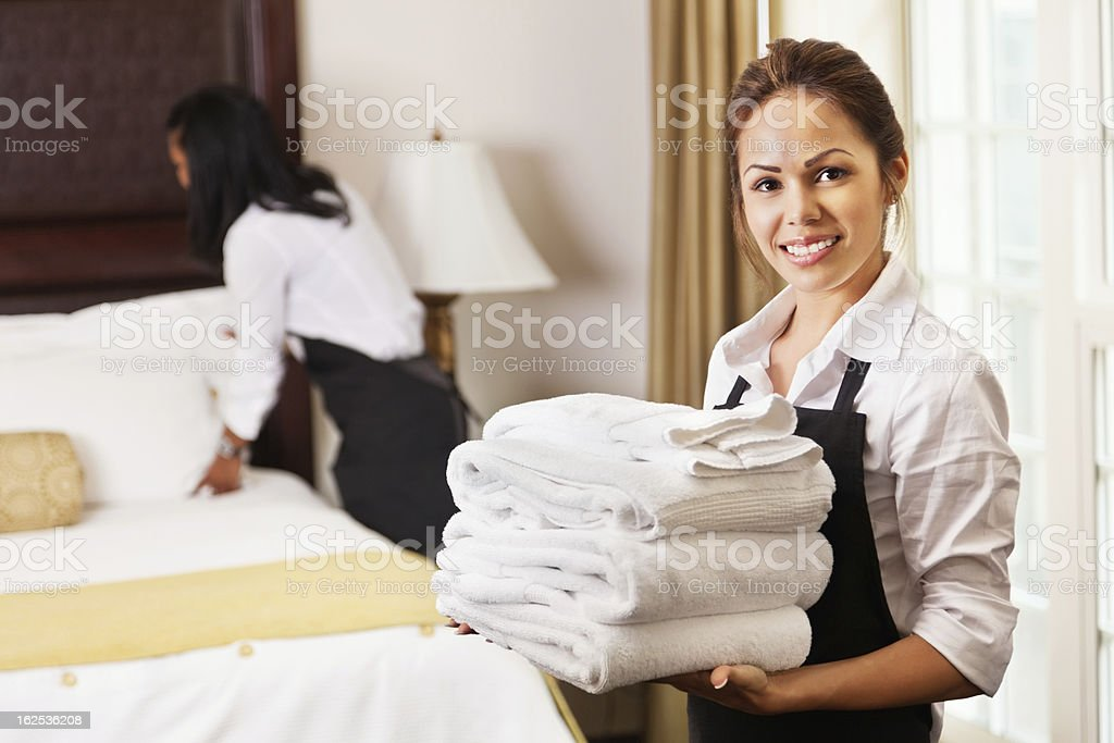 Young maids cleaning and preparing room for hotel guests stock photo