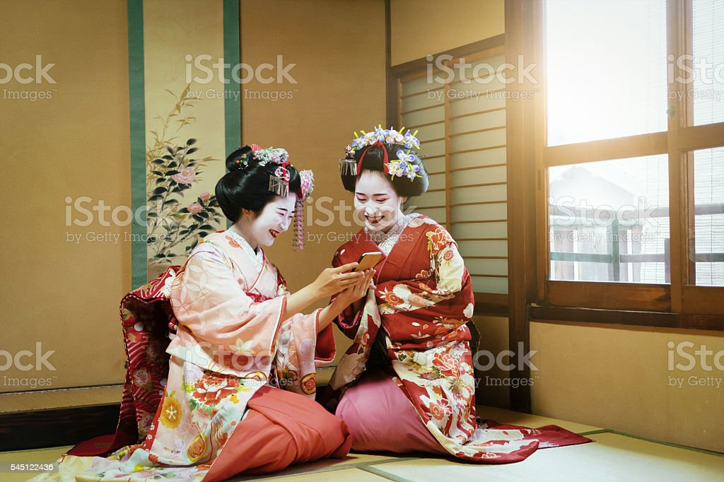 Young Maiko Having Fun Together With Smartphone stock photo