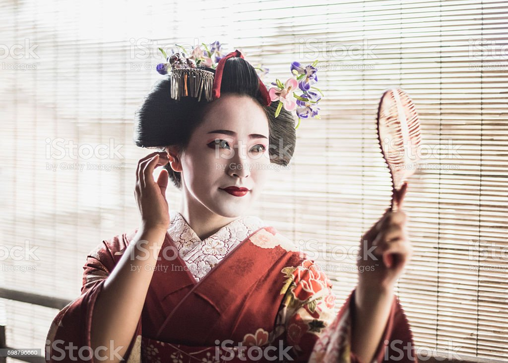 Young maiko in kimono adjusting hair holding mirror stock photo