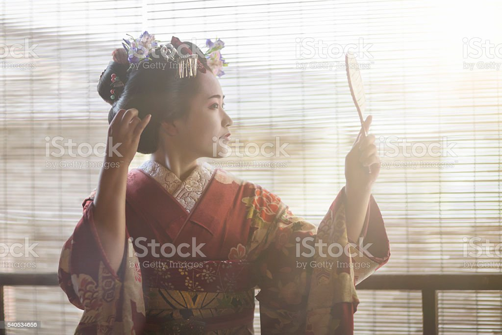 Young Maiko looking herself at a hand mirror stock photo