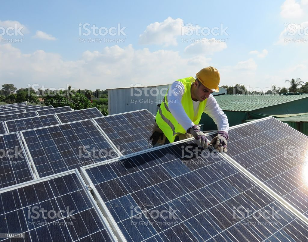 Young maintenance worker installing solar panels on rooftop stock photo