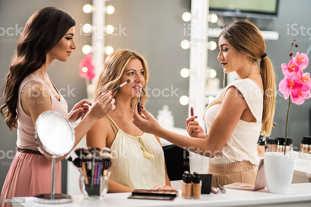 Young make-up artists working on beautiful woman in beauty salon. stock photo