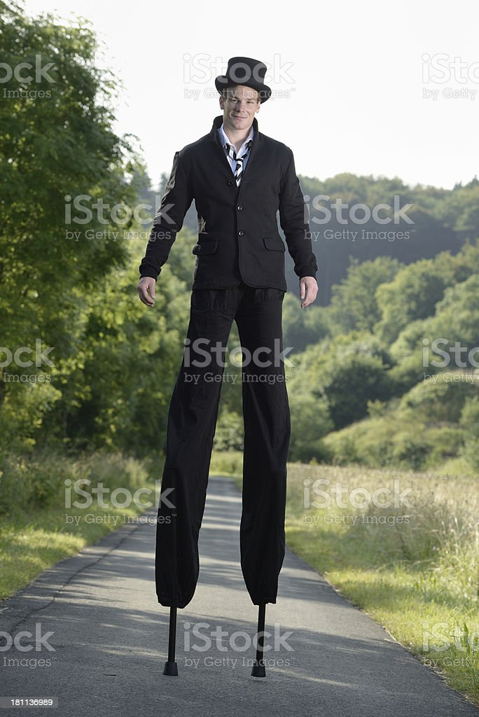 young mal artist on stilts stock photo