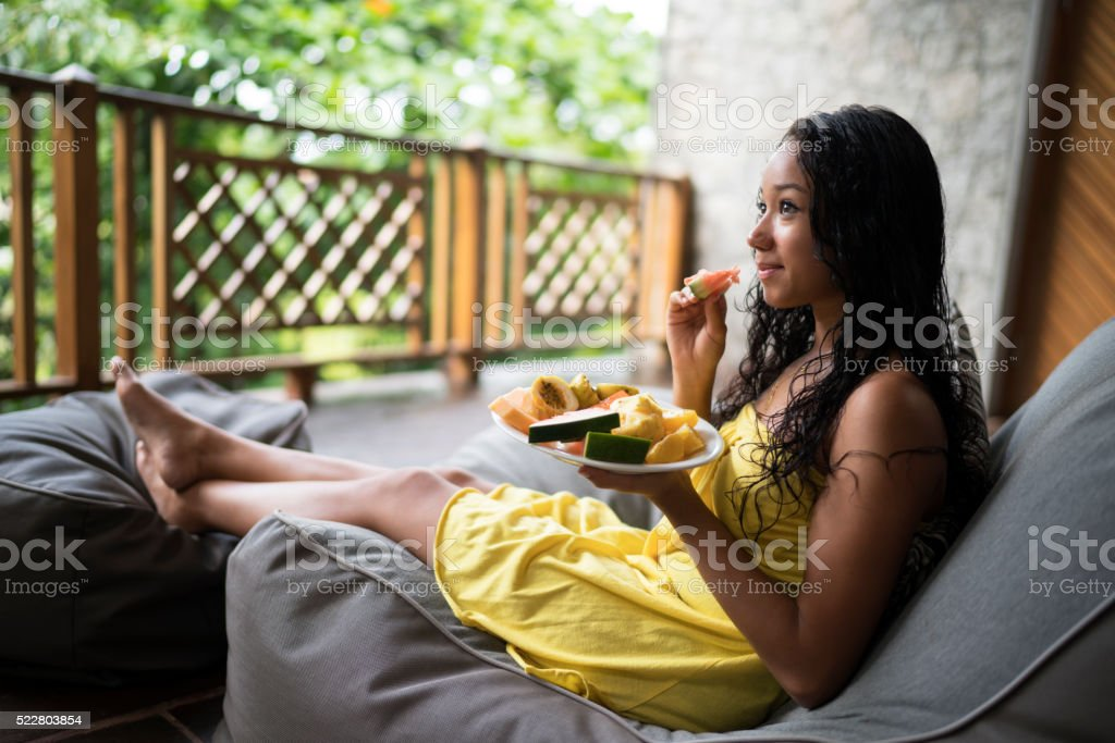 Young Malaysian woman eating fresh fruit on a balcony. stock photo