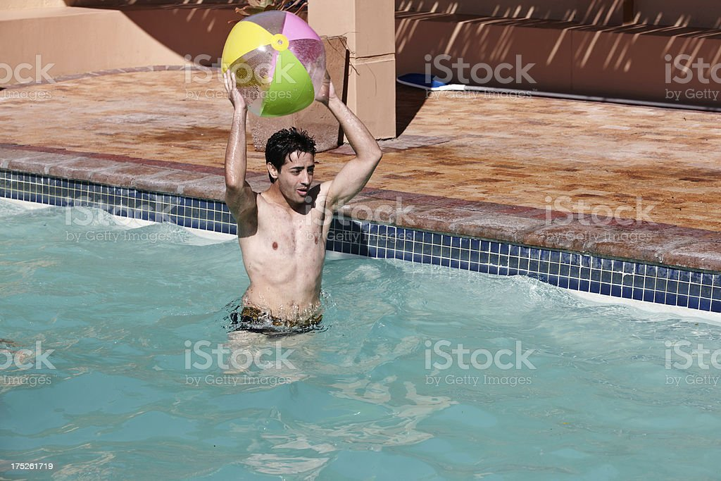 Young male adult playing with beach ball in pool royalty-free stock photo