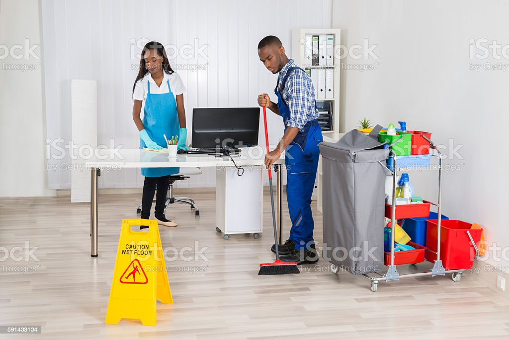Young Male And Female Cleaners Cleaning Office stock photo