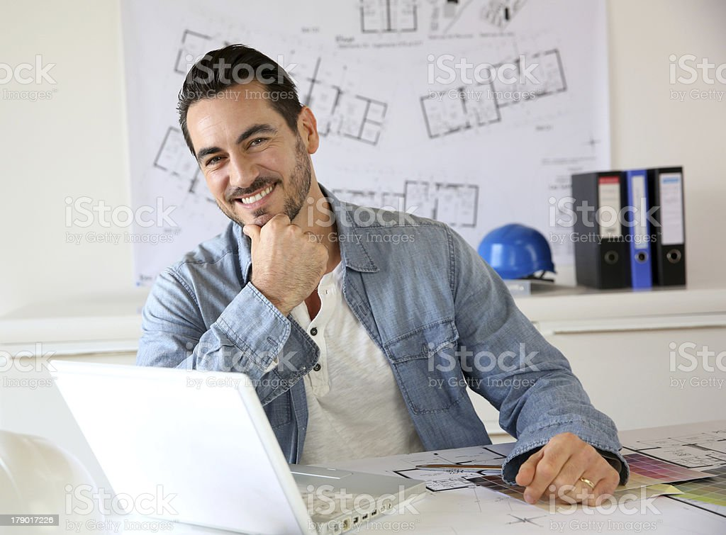 Young male architect smiling in front of his laptop royalty-free stock photo