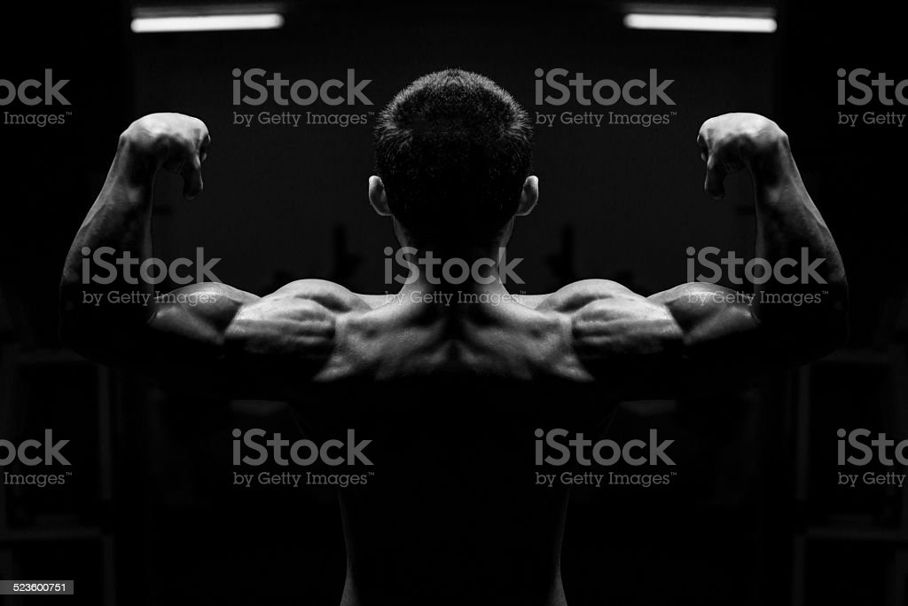 Young Male Athlete Flexing Back Muscles stock photo